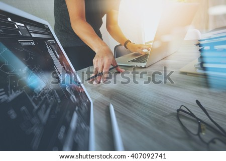 designer hand working with digital tablet and laptop and notebook stack and eye glass on wooden desk in office #407092741