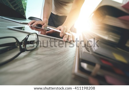 designer hand working with digital tablet and laptop computer and book stack and eye glass on wooden desk as concept