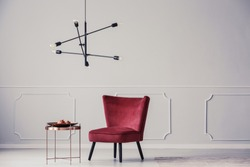 Designer lamp above copper table next to red armchair in bright apartment interior