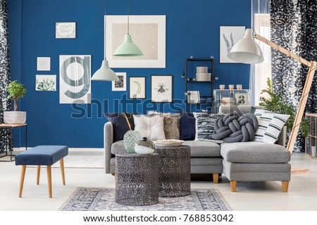 Designer metal tables in living room with navy blue stool near grey corner sofa and lamp
