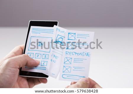 Designer prototyping mobile application, sketches of mobile screens, responsive websites #579638428