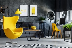Designer's yellow chair next to simple table in living room with work area next to the window