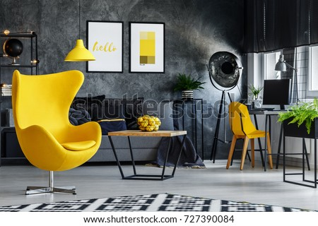 Designer's yellow chair next to simple table in living room with work area next to the window #727390084
