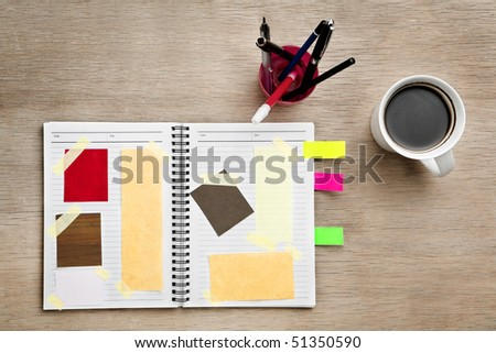 Designer scrap book, filled with various paper and material on wooden table, placed with mug of coffee and pen holder