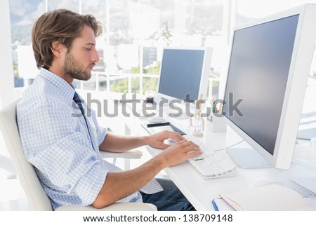 Designer sitting at his desk and working in bright modern office