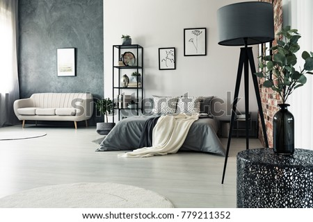 Designer table and grey lamp in multifunctional bedroom with king-size bed and sofa against walls with posters