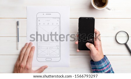 Designer tests the user interface and user experience on a mobile phone. Wireframe beside with mobile phone with a sketched app. The concept of designing software, apps and websites. #1566793297