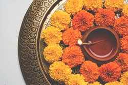 Designer Thali decorated with Marigold flowers around Clay Oil Lamp or Diwali Diya, over white background. selective focus