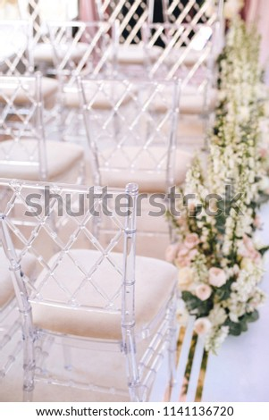 Designer transparent chairs with rhombus pattern vvide in the area of wedding decoration Flower arrangements. Vertical #1141136720