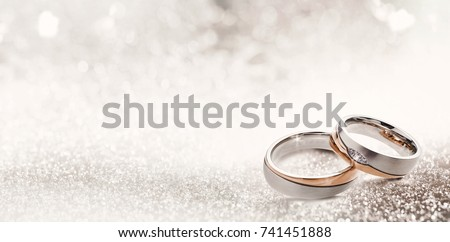 Designer wedding rings in the corner on a sparkling glitter background in panoramic banner format with copy space and selective focus