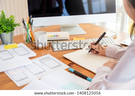 Designer woman drawing a website outline and website ux app development on mobile phone. #1408125056