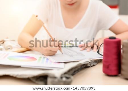 Designer working, Dressmaker, Designer, Woman tailor is sketching to design and check dress color