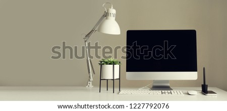 Designer workspace. Minimalistic home office. Blank screen desktop computer. Desktop computer, lamp, graphics tablet, keyboard, mouse, pen, succulent plant on white desk. Copy space. #1227792076