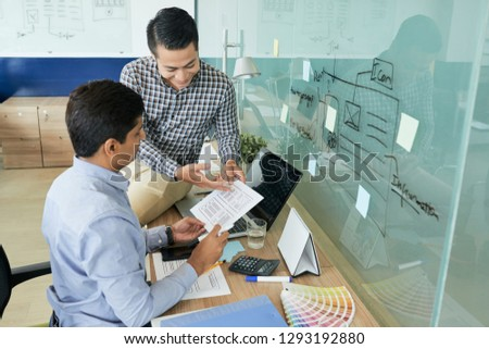 Designers discussing webpage template and color scheme at meeting #1293192880