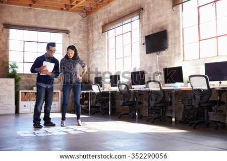 Designers Planning Layout On Floor Of Modern Office