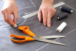 Designing clothes, applying a template to a textile fabric, preparing for cutting and sewing. A tailor draws a line with chalk on a textile cloth, and professional scissors, a ruler, and bobbins of co