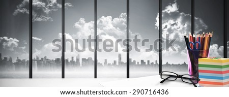 desk against room with large window looking on city skyline