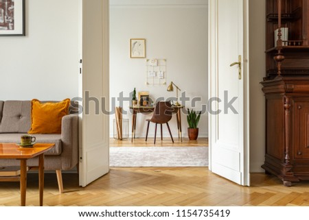 Desk and chair in a home office interior. View through door of a vintage living room. Real photo