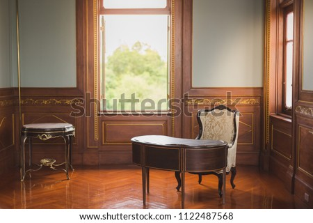 Desk and chair in antique office with warm lighting from windows #1122487568