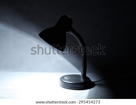 Desk Lamp on Table in the Dark Room