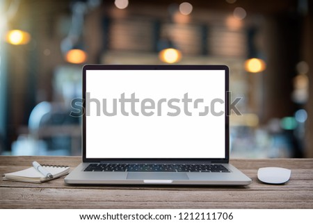 Desk Laptop with blank screen on table of coffee shop blur background with bokeh