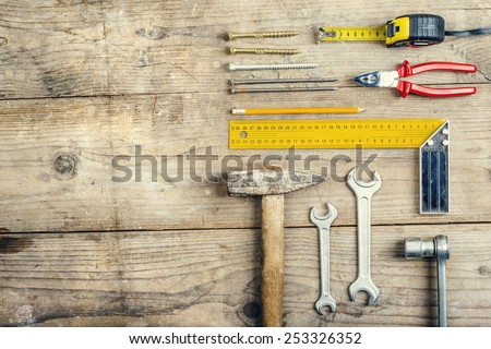 Desk of a carpenter with a hammer and two nails. Studio shot on a wooden background. #253326352
