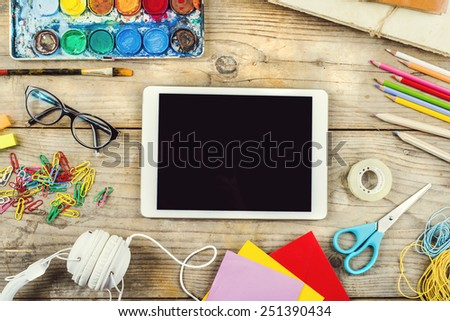 Desk of an artist with lots of stationery objects. Studio shot on wooden background.