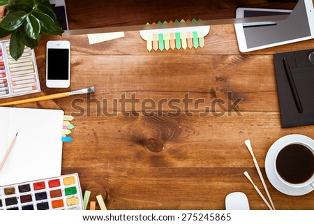 Desk of an artist with lots of stationery objects. Studio shot on wooden background.Top view.