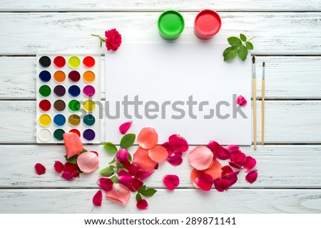 Desk of creative worker. Paints, brush, paper, rose petals and leaves. Top view background.