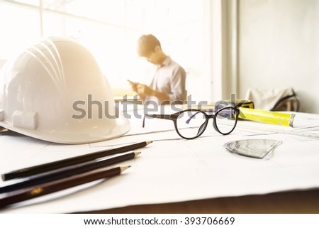 Desk of Engineering project in construction site or office with mining light.Construction concept.Engineering tools.Vintage tone retro filter effect,soft focus(selective focus)