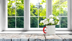 Desk of free space with spring flowers and background of window