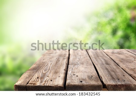 desk of wood in retro color and green space of garden sunset