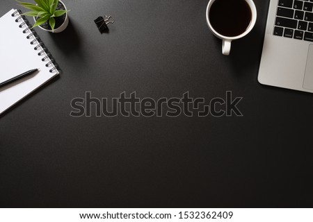 desk office top view with computer,notepad, pen coffee and plant on black background. flat lay with copy space.