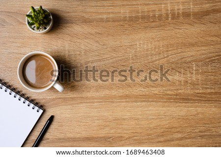 desk office with blank notepad, coffee cup and pen on wood table. Flat lay top view copy spce.