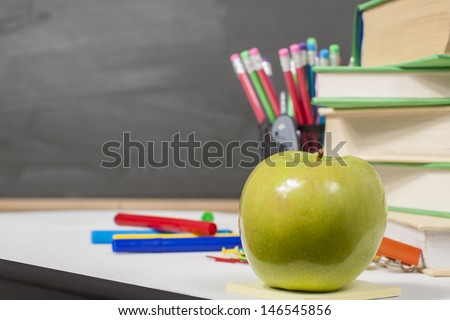 desk with a green apple ,color pencils,books and other equipment