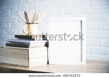 Desk with blank picture frame and pencils in iron mug placed on books and wooden box. Mock up