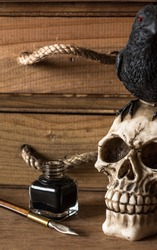 desk with fountain pen, inkwell and skull with crow