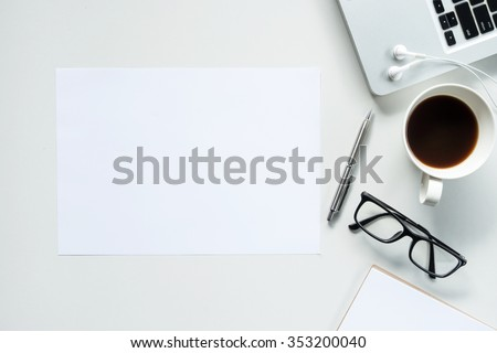 Desk with laptop, eye glasses, earphone, pen and a cup of coffee, top view. The blank paper can be used to put some text or images. #353200040
