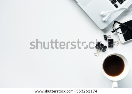 Desk with laptop, eye glasses, earphone, pen, document clips and a cup of coffee. Top view with copy space. #353261174