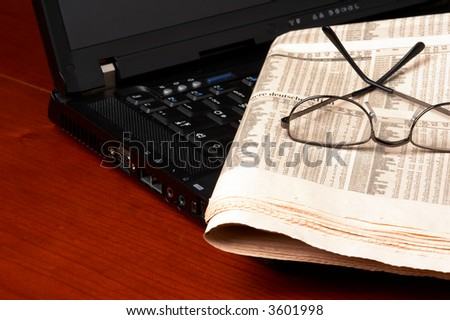 Desk with laptop, newspaper, glasses