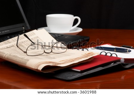 Desk with laptop, ring binder, newspaper, glasses and a cup of coffee