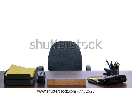 Desk with nobody sat at it, against a white background. Blank name sign to add your own text. - stock photo