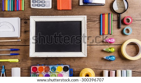Desk with stationary and a picture frame. Studio shot on wooden background.