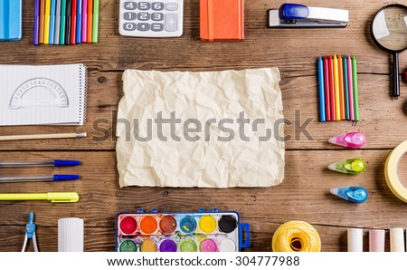 Desk with stationary and blank sheet of paper. Studio shot on wooden background.