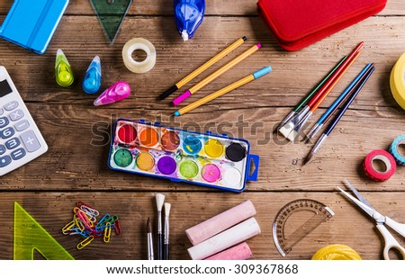 Desk with stationary and with Back to school sign. Studio shot on wooden background. stock photo