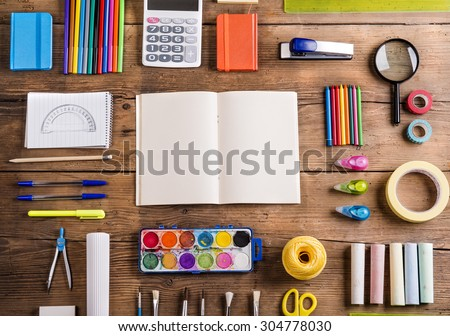 Desk with stationary and with blank notebook. Studio shot on wooden background.