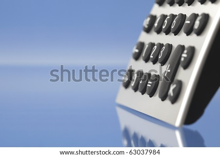 Desktop calculator, closeup on blue background