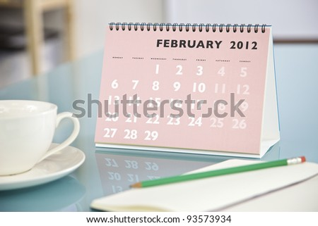 Desktop calendar sitting on a glass desk showing the month of February 2012