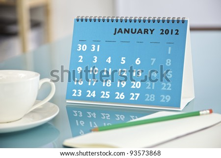 Desktop calendar sitting on a glass desk showing the month of January 2012