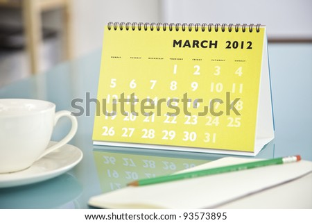 Desktop calendar sitting on a glass desk showing the month of March 2012 - stock photo